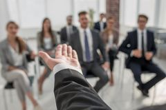 Rear view.Business coach gesturing his hand in front of a group of people. Close up royalty free stock image