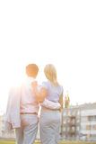 Rear view of business couple standing with arms around against clear sky on sunny day Stock Photo