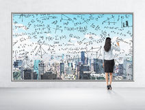 Rear view of business lady who is drawing math formulas on the New York panoramic poster. Royalty Free Stock Images