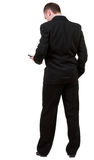 Rear view of business man in black suit  talking on mobile phon Stock Photo