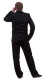 Rear view of business man in black suit  talking on mobile phone Royalty Free Stock Image