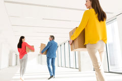 Rear view of business people with cardboard boxes moving into new office stock photos