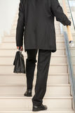 Rear view of a business person ascending the stairs Stock Photos