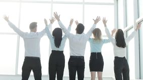 Rear view. business team with hands up standing in front of office window stock photography