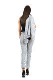 Rear view of business woman in formal wear holding jacket walking away. Full body length portrait isolated over white studio background Stock Photography