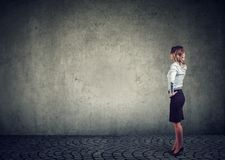 Rear view of business woman standing by the wall with hand on head wondering what to do next being challenged. Full length of royalty free stock image