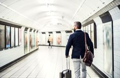 Rear view of businessman with a bag and suitcase walking in subway. stock images