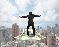Rear view businessman balancing on money flying carpet Stock Images