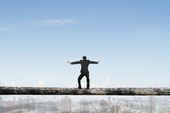 Rear view businessman balancing on tree trunk high in sky Royalty Free Stock Image