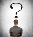 Rear view of businessman with big question mark Stock Images