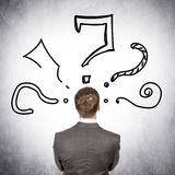 Rear view of businessman with big question marks. On grey wall background Stock Photos