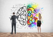 Business people drawing brain on concrete. Rear view of a businessman and a businesswoman drawing a colorful large brain sketch on a concrete wall. Concept of Stock Photo