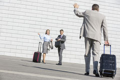 Rear view of businessman carrying luggage waving hand to colleagues Stock Photography