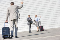 Rear view of businessman carrying luggage waving hand to colleagues Royalty Free Stock Image