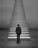 Rear view businessman climbing on stairs with spot lighting Royalty Free Stock Photo