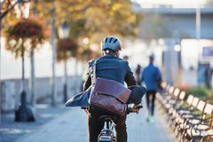 A rear view of businessman commuter with electric bicycle traveling to work in city. A rear view of a businessman commuter with electric bicycle traveling to stock images