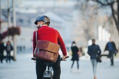 A rear view of businessman commuter with electric bicycle traveling to work in city. A rear view of a businessman commuter with electric bicycle traveling to stock image