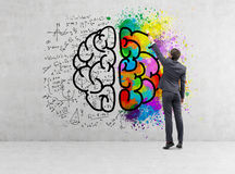 Rear view of businessman drawing colorful brain icon on concrete. Rear view of a businessman drawing a giant brain sketch with formulas and colors on a concrete stock photo