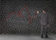 Rear view of a businessman drawing a red line through black maze Stock Photo