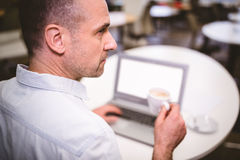 Rear view of businessman drinking coffee at creative office Stock Images