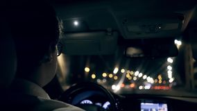 Rear view of a businessman driving a car through a night tunnel. Rear view of an unrecognizable young businessman wearing a white shirt and glasses driving his stock video
