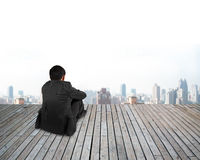 Rear view businessman hands holding knee sitting with urban scen Stock Photo
