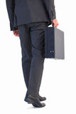 Rear view of businessman holding briefcase walking Stock Photos