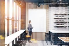Businessman in a bar interior. Rear view of a businessman holding a paper cup of coffee and looking at a large poster hanging on a bar wall near a stand. 3d Stock Image