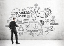 Rear view of businessman looking at business plan Stock Images