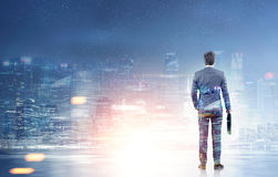 Rear view of a businessman looking at a night city. Rear view of a businessman holding a suitcase and looking at a night cityscape. Toned image double exposure Stock Photo