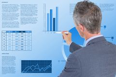 Rear view of businessman making graph while working in office. Digital composite of Rear view of businessman making graph while working in office Royalty Free Stock Images