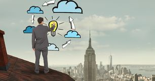 Rear view of businessman on roof drawing clouds and bulb in midair Stock Photography