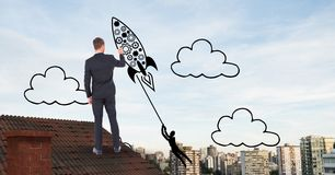 Rear view of businessman on roof drawing rocket in midair Stock Images