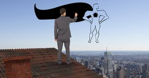 Rear view of businessman on roof drawing super hero in midair Stock Photography