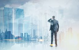 Rear view businessman scratching head, blue city royalty free stock photo