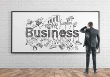 Rear view businessman scratching head, business stock image