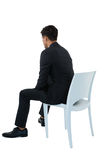 Rear view of businessman sitting on chair. Against white background Royalty Free Stock Image