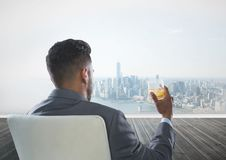 Rear view of businessman sitting on chair holding glass of alcohol while looking at city Stock Photography