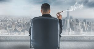 Rear view of businessman sitting on chair and looking at city while smoking cigar. Digital composite of Rear view of businessman sitting on chair and looking at Stock Photography