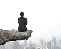 Rear view businessman sitting on cliff with urban skyscrapers Stock Image