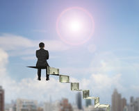 Rear view businessman sitting on top of money stairs stock photos