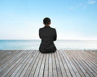 Rear view businessman sitting on wooden floor with sky sea Royalty Free Stock Photography