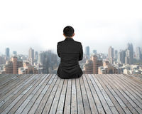 Rear view businessman sitting on wooden floor with urban scene Stock Images