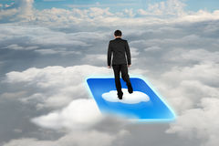 Rear view businessman standing on cloud icon with cloudscape background royalty free stock photography