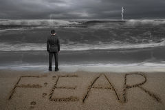 Rear view businessman standing facing fear word on sand beach. Rear view of black suit businessman standing facing fear word written on sand beach dark stormy Stock Photo