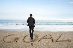Rear view businessman standing with goal word on sand beach. Rear view of black suit businessman standing with goal word written on sand beach background Royalty Free Stock Photos