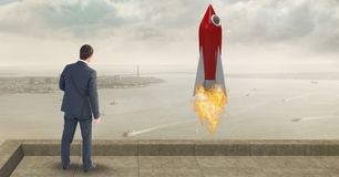 Rear view of businessman standing by rocket launch while looking at sea Stock Image