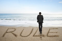 Rear view businessman standing with rule word on sand beach. Rear view of black suit businessman standing with rule word written on sand beach background Stock Photo