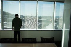 Rear view of businessman standing by window in meeting room Stock Photo
