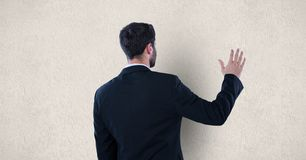 Rear view of businessman touching wall Royalty Free Stock Photos